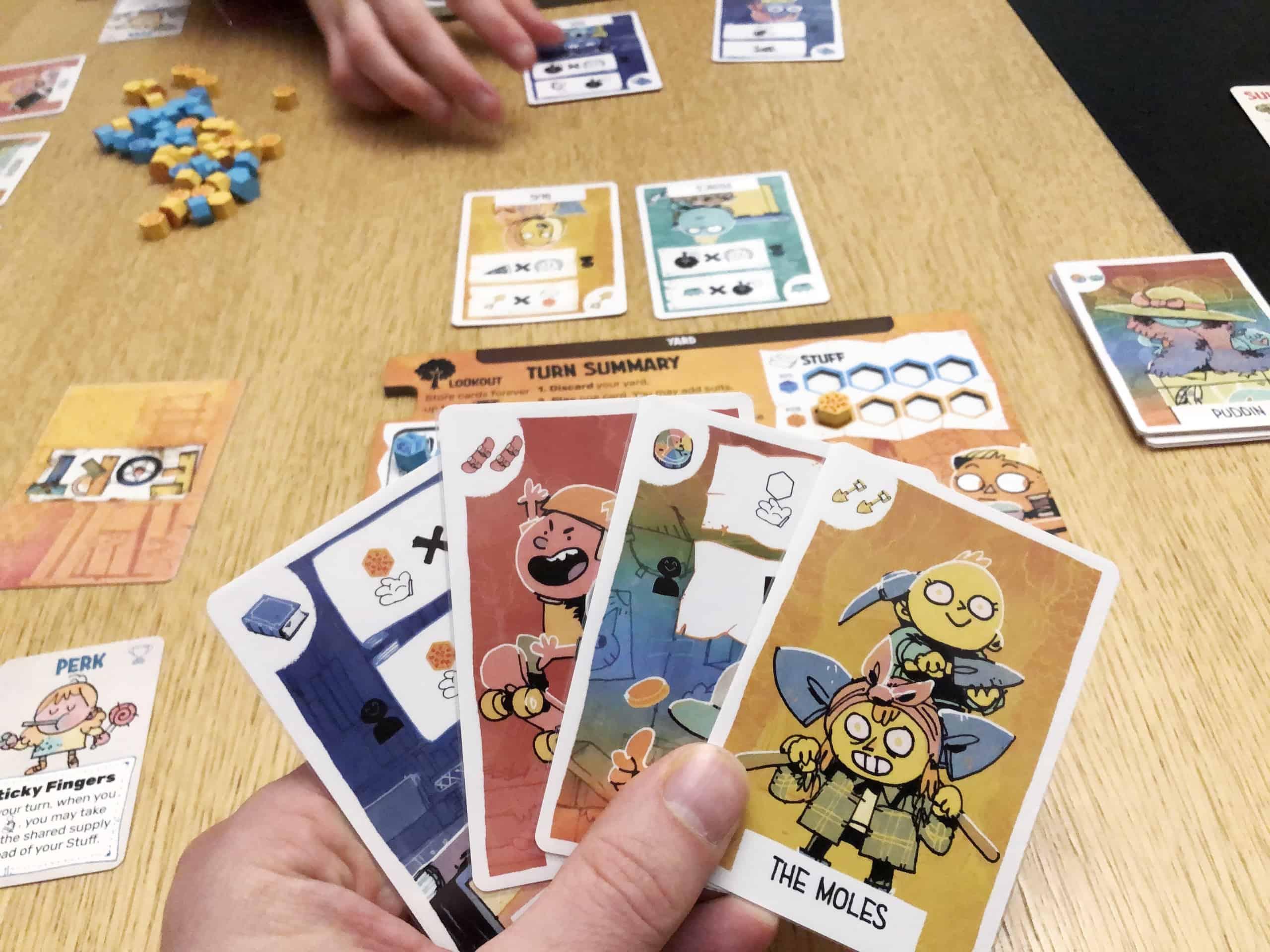 Neljä korttia kädessä, taustalla pelilauta