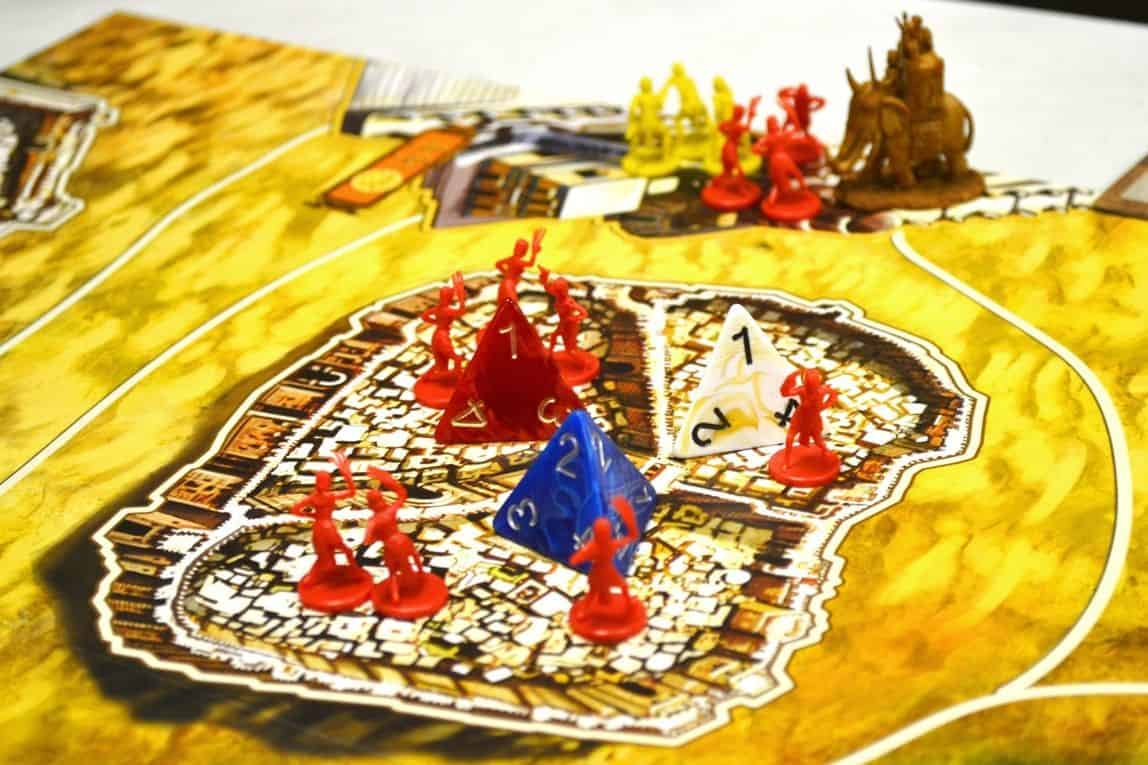 Etualalla punaisen pelaajan kaupunki, jossa noppia ja nappuloita, taustalla taistelua